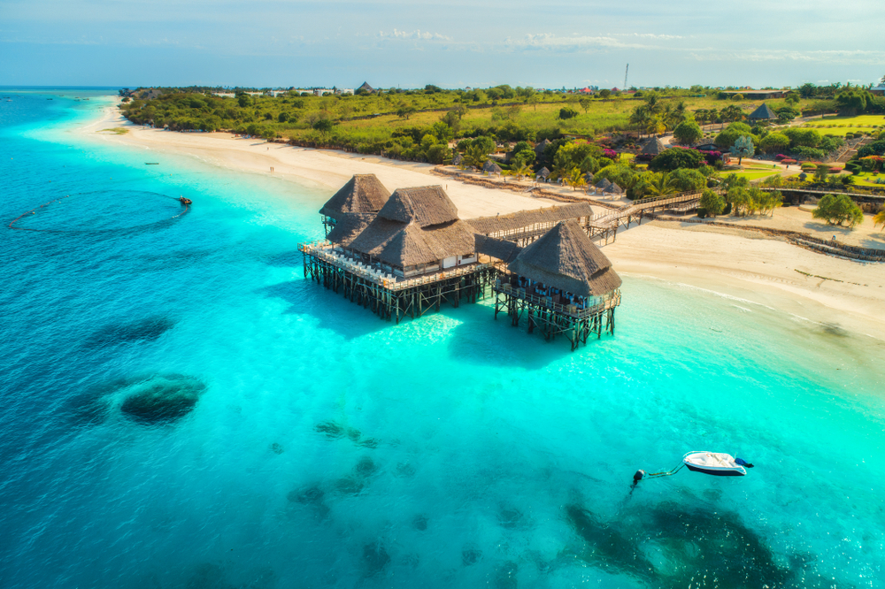 ST Aerial view of beautiful hotel in Indian ocean at sunset in summer. Zanzibar Africa. Top view. Landscape with wooden hotel on the sea azure water sandy beach green trees boat. Luxury resort