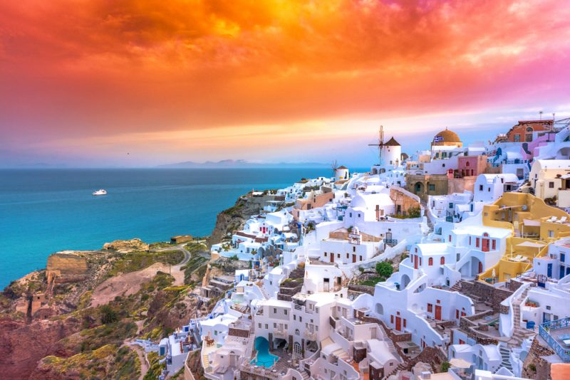 ST Oia town on Santorini island Greece. Traditional and famous houses and churches with blue domes over the Caldera Aegean sea