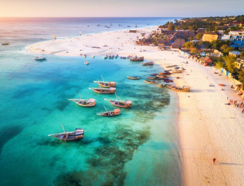 ST tropical sea coast with sandy beach at sunset. Summer holiday on Indian Ocean Zanzibar Africa