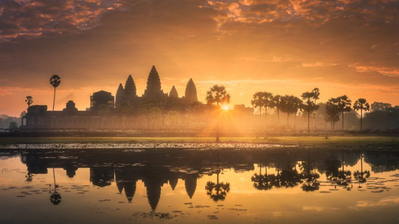 ST Sunrise view of popular tourist attraction ancient temple complex Angkor Wat with reflected in lake Siem Reap Cambodia 1